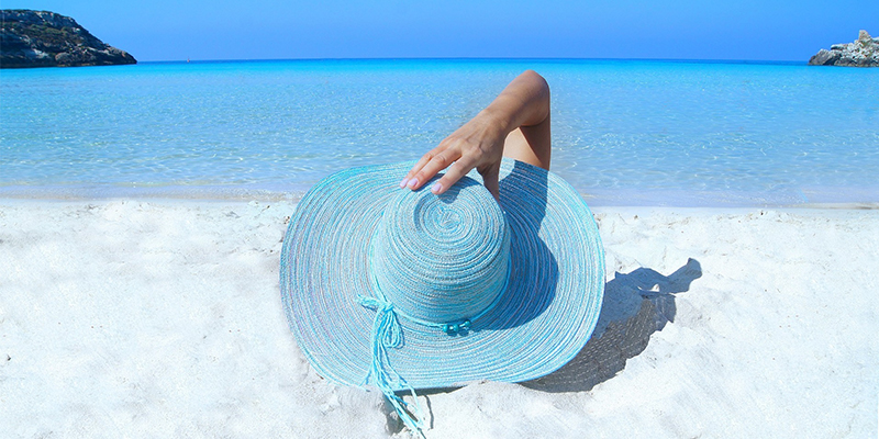 Blue-sun-hat-on-white-sand-beach-clear-blue-sea