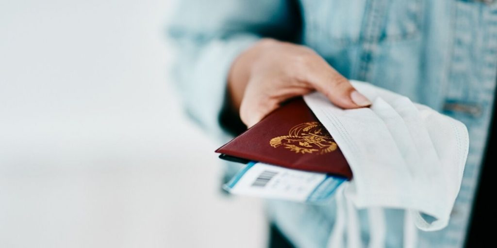 Woman holding passport and face mask