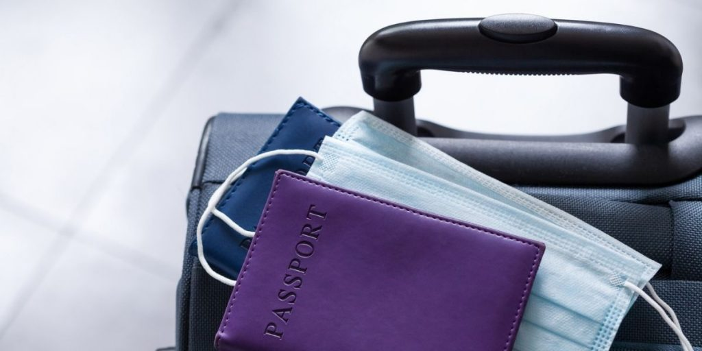 suitcase with facemask and passport covid