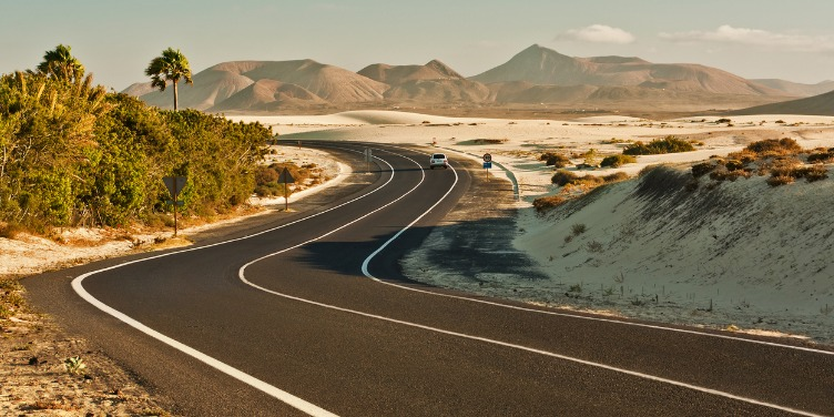 an image of a winding road in the desert with mountains in the background