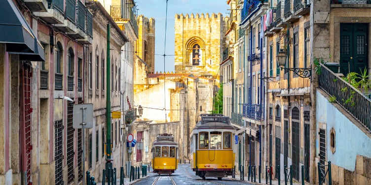 an image of two trams transporting people up and down the hilly streets of Lisbon